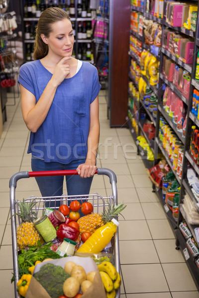 Zamyślony pretty woman popychanie przejście supermarket kobieta Zdjęcia stock © wavebreak_media