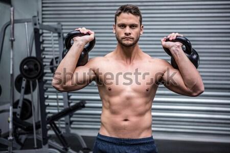 Muscular man lifting two kettlebells Stock photo © wavebreak_media