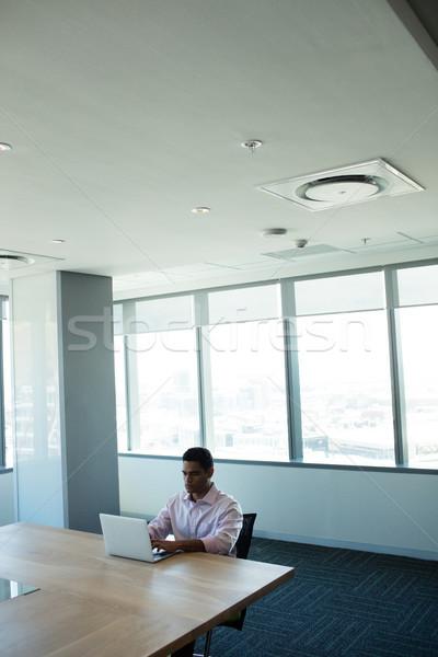 Imprenditore digitando laptop sala conferenze seduta tavola Foto d'archivio © wavebreak_media