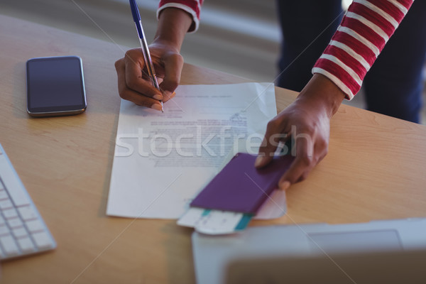 Businesswoman signing documents on desk in office Stock photo © wavebreak_media