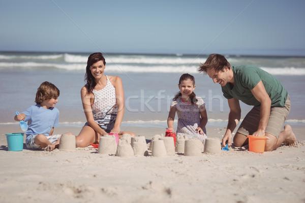 Happy family making sand castle at beach Stock photo © wavebreak_media