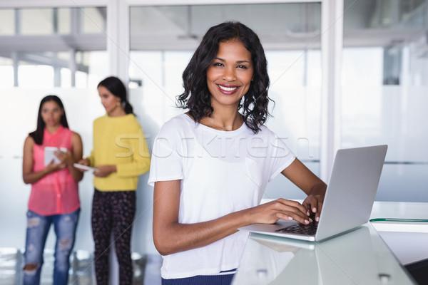 Portrait of smiling businesswoman using laptop Stock photo © wavebreak_media