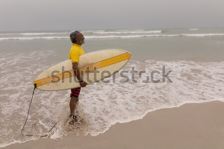 Vista posteriore senior uomo indossare piedi tavola da surf Foto d'archivio © wavebreak_media