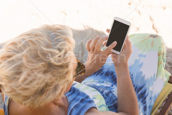 High angle view of woman using smart phone while sitting on chair Stock photo © wavebreak_media