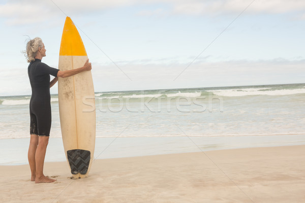 Rear view of senior woman holding surfboard while standing on shore Stock photo © wavebreak_media