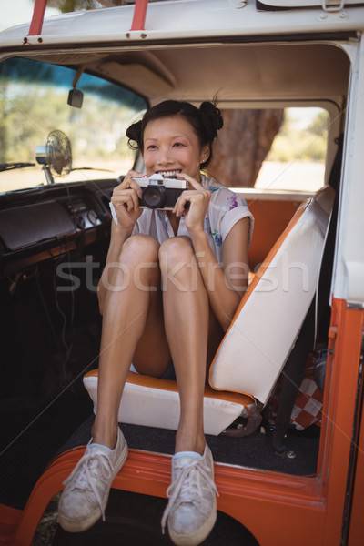 Cheerful woman holding camera while sitting in motor home Stock photo © wavebreak_media