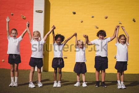 Trainer assisting kids in climbing wall Stock photo © wavebreak_media