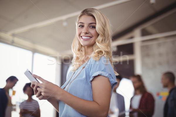 Smiling businesswoman holding mobile phone in creative office Stock photo © wavebreak_media