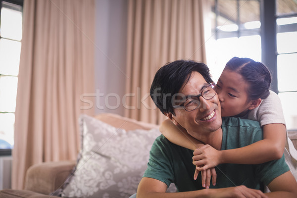 Daughter kissing father on cheeks in living room Stock photo © wavebreak_media