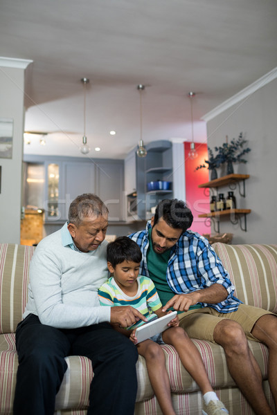 Boy using tablet while sitting with father and grandfather Stock photo © wavebreak_media