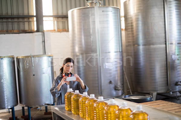 Femenino trabajador toma foto petróleo botellas Foto stock © wavebreak_media