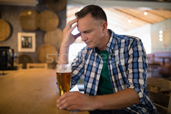 Worried man sitting at bar with glass of beer Stock photo © wavebreak_media