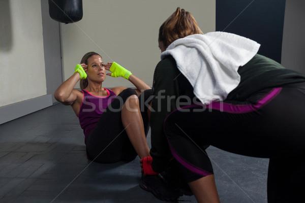 Trainer assisting woman in exercise Stock photo © wavebreak_media