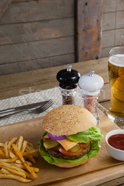 Stock photo: Hamburger, french fries, tomato sauce and glass of beer on chopping board