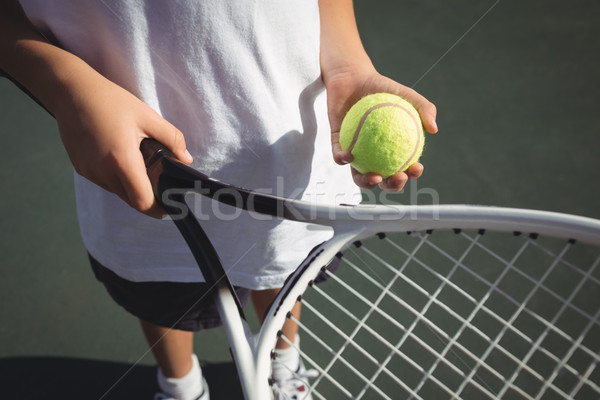 Midsection of girl holding tennis racket and ball Stock photo © wavebreak_media