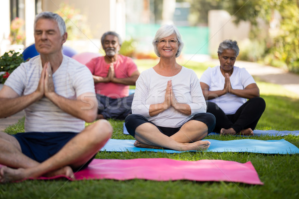 Sorridente senior mulher meditando oração posição Foto stock © wavebreak_media