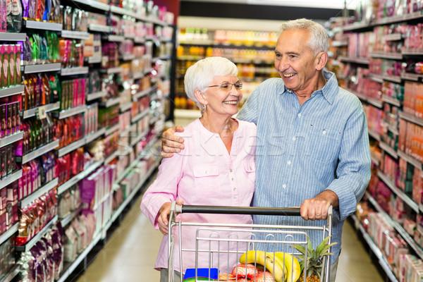 Senior couple embracing while pushing cart Stock photo © wavebreak_media