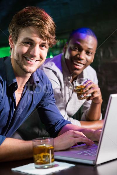 Two men having whiskey and using laptop at bar counter Stock photo © wavebreak_media