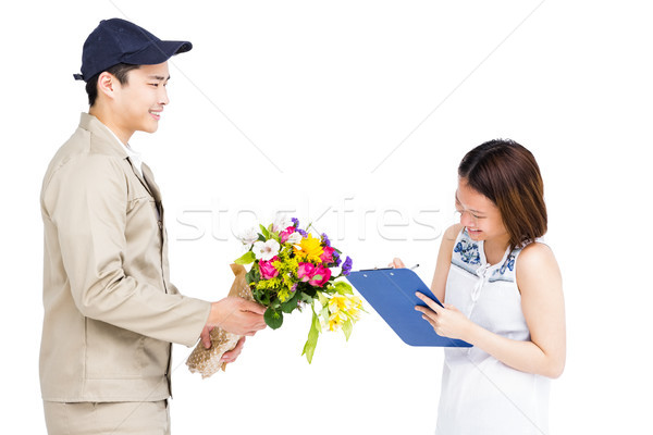Delivery man taking signature of woman while delivering flowers Stock photo © wavebreak_media