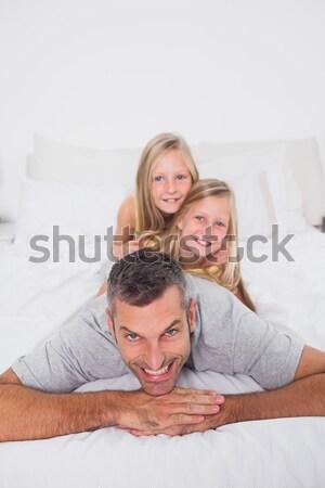 портрет улыбаясь счастливая семья кровать расслабляющая домой Сток-фото © wavebreak_media