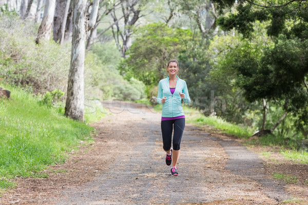 Cheerful young woman jogging in forest Stock photo © wavebreak_media
