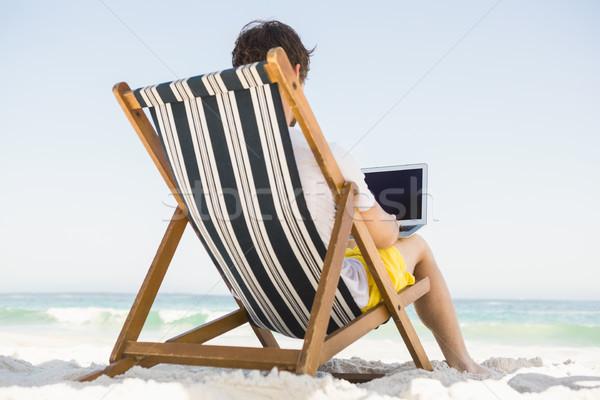 Foto stock: Hombre · relajante · usando · la · computadora · portátil · playa · tecnología · océano