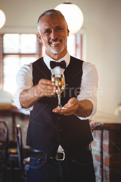 Smiling bartender offering a glass of wine at bar counter Stock photo © wavebreak_media
