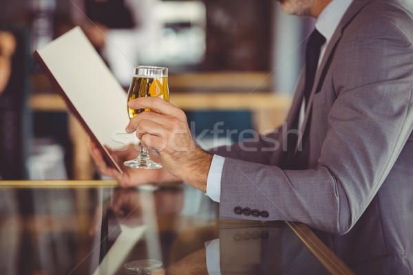 Businessman holding glass of beer and looking at menu Stock photo © wavebreak_media