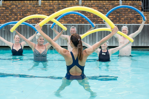 Instructor and senior swimmers exercising with pool noodle Stock photo © wavebreak_media