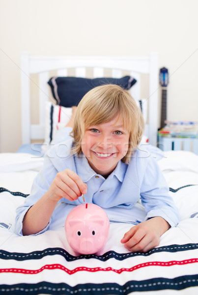 Sorridente menino moeda cama Foto stock © wavebreak_media