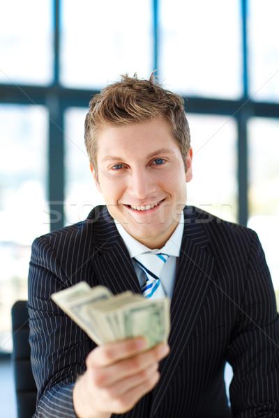 Junior businessman holding dollars and smiling at the camera Stock photo © wavebreak_media