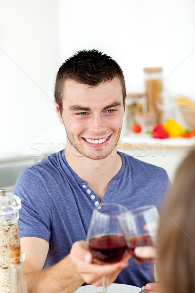Handsome young man having diner with his girlfriend drinking wine at home in the kitchen Stock photo © wavebreak_media