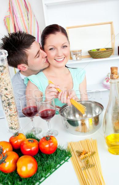 Bright couple preparing spaghetti in the kitchen and drinkng wine Stock photo © wavebreak_media