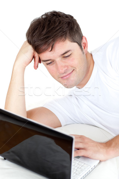 thoughful man using his laptop lying on the ground against a white background Stock photo © wavebreak_media