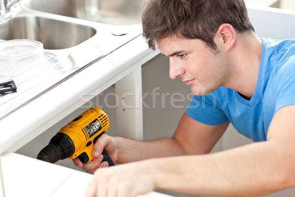 Self-assured man holding a drill repairing a kitchen sink Stock photo © wavebreak_media
