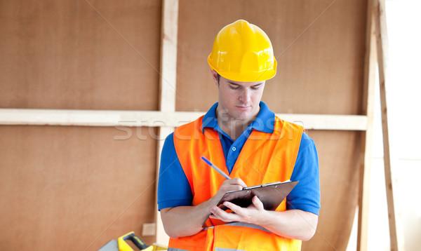 Self-assured male worker writing on a clipboard at work Stock photo © wavebreak_media