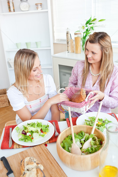 Young woman giving bread to her friend while eating salad in the kitchen Stock photo © wavebreak_media