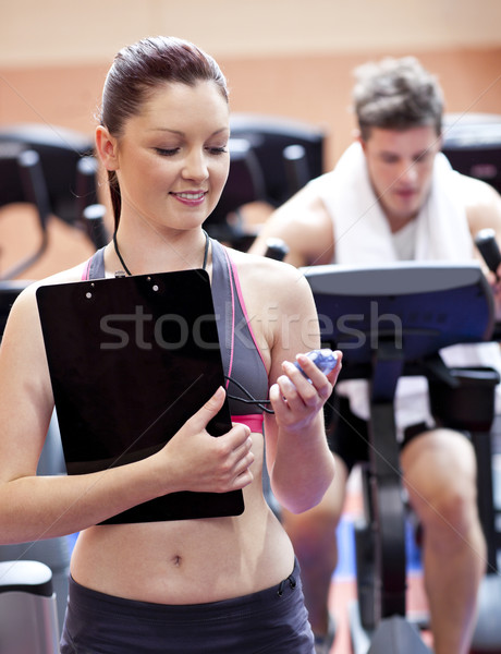 Joyful coach holding a chronometer with man in the background doing physical exercises in a fitness  Stock photo © wavebreak_media