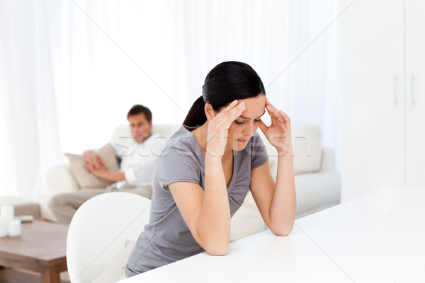 Tired woman having a headache sitting at a table in the lliving room with her boyfriend Stock photo © wavebreak_media