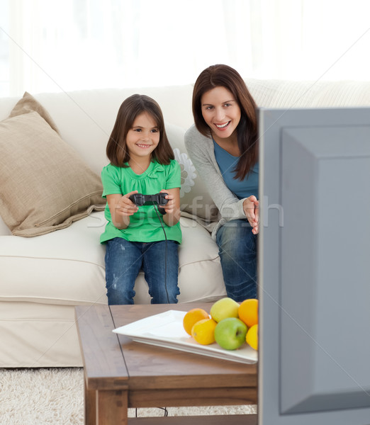 Pretty mom encouraging her daughter playing video games in the living room Stock photo © wavebreak_media