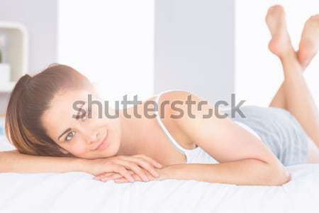 Pretty woman lying down on her bed Stock photo © wavebreak_media