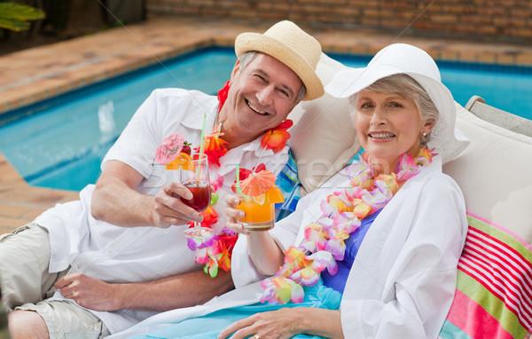 Volwassen paar drinken cocktail naast zwembad Stockfoto © wavebreak_media