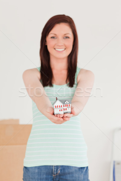 Gorgeous red-haired female holding a miniature house while standing on the floor at home Stock photo © wavebreak_media
