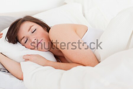 Attractive brunette female having a rest while lying on a bed Stock photo © wavebreak_media