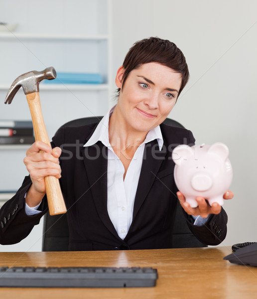 Smiling office worker breaking a piggybank with a hammer in her office Stock photo © wavebreak_media