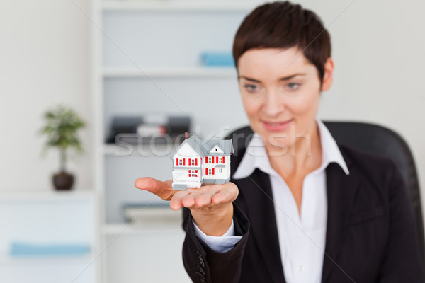 Young brunette showing a house miniature in her office Stock photo © wavebreak_media