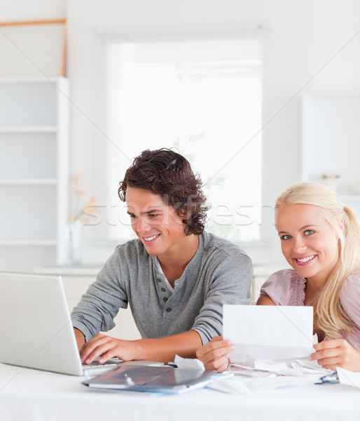 Happy couple with bills and laptop in their living room Stock photo © wavebreak_media