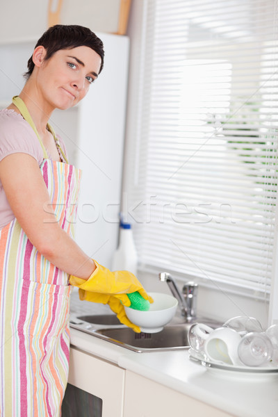 Woman washing the dishes looking into the camera in the kitchen Stock photo © wavebreak_media