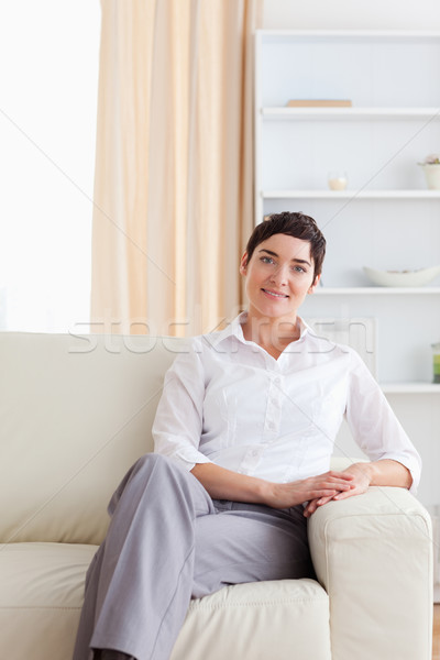 Charming woman sitting on a sofa in the living room Stock photo © wavebreak_media