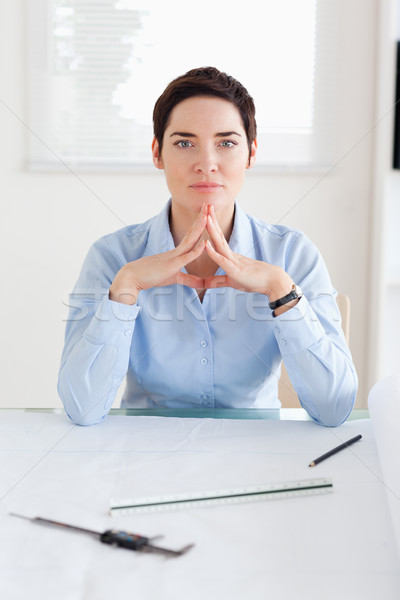 Thoughtful Woman with an architectural plan looking into the camera in an office Stock photo © wavebreak_media